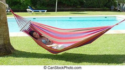 Woman in hammock at tropic resort with pool