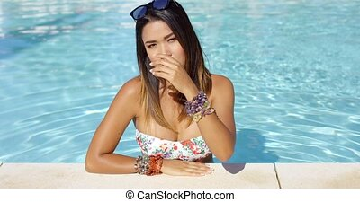 Beautiful young woman relaxing in a swimming pool -...