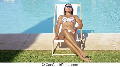 Relaxed woman sunbathing in a deck chair - Relaxed pretty...