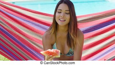 Smiling young woman holding one watermelon slice while...