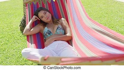 Single beautiful woman laying down in hammock - Single...