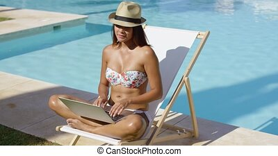 Fashionable young woman relaxing at the pool sitting...