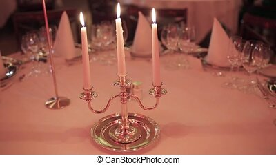 Candlestick with three burning candle on served restaurant...