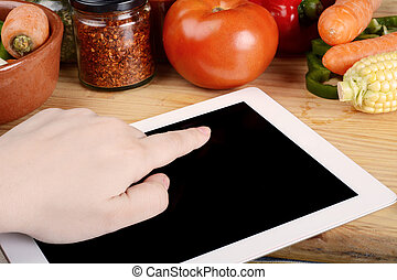 Person preparing food from recipe on tablet - Person...