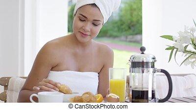 Woman in towel dipping donut in coffee - Single beautiful...