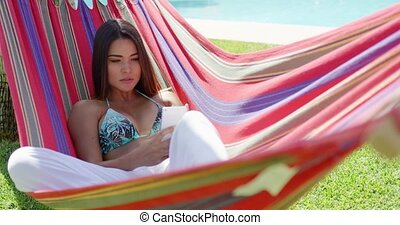 Woman sitting back in hammock while using phone - Beautiful...