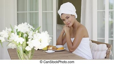 Young woman sitting having breakfast on her patio - Young...