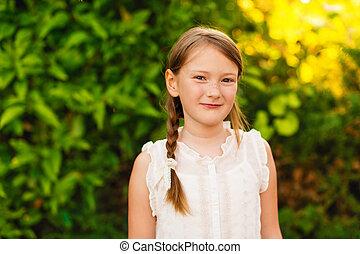 Little girl in the summer garden at sunset