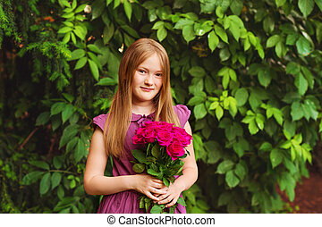 Portrait of adorable little girl of 8-9 years old, holding...