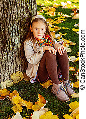 Autumn portrait of adorable little blond girl of 8 years...