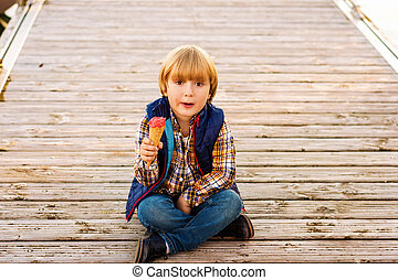 Cute little boy eating ice cream outdoors