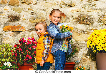 Autumn portrait of two adorable kids, little girl and boy,...