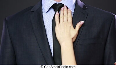 girl straightens his tie to her husband.