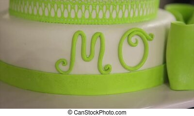 "green wedding cake with word ""MO"""