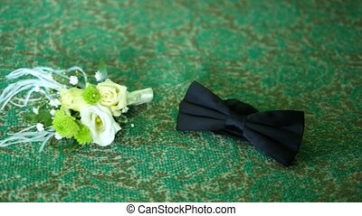 A black bow tie and pretty boutonniere on a green background...