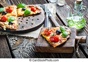 Close-up of freshly baked pizza with tomatoes and olives