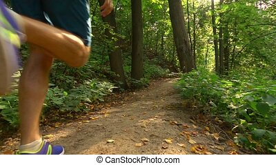 Runner speeding uphill in the forest. Super slow motion...