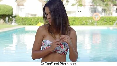 Thoughtful young woman in a summer bikini standing in front...