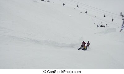 Snowboarders ride on snowmobile holding rope. Ski resort....