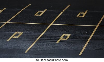 Drops of rain fall on black surface of parking space on...