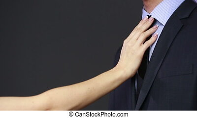 girl straightens his tie to her husband. preparation for...