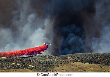 White Aircraft Dropping Fire Retardant as it Battles the...