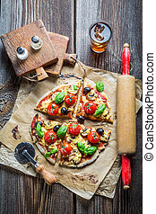 Closeup of baked pizza with olives and tomatoes