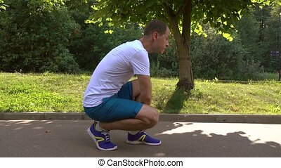 Male runner ties the laces and starts running down the park...