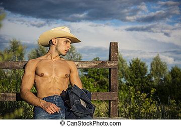 Portrait of rustic man in hat shirtless leaning on wooden...