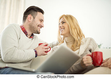 Couple relaxing on sofa in free time - Couple sitting on...