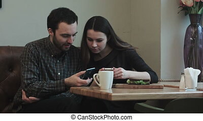 Two young people looking into smartphones while sitting at a table in cafe