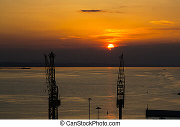 Cranes in harbor during sunset