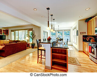 Open floor plan. Kitchen room interior with light brown cabinets