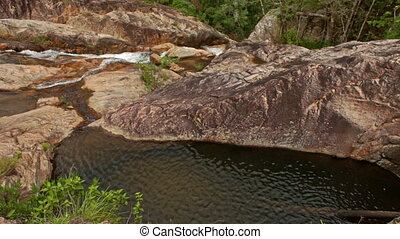 View of Deep Oval Pool among Rocks against Foamy Stream -...