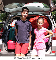 brother and sister near the trunk of the car before leaving...
