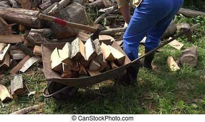 Male villager load chopped wood firewood and axe to rusty...