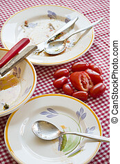 fresh tomatoes on a table with dirty plates - fresh...
