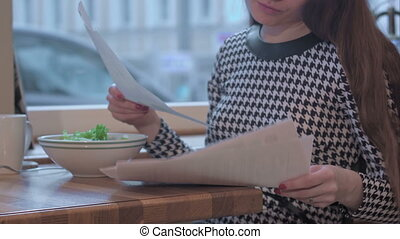Arms of young businesswoman reading documents. She is sitting at the table in cafe and eating a salad