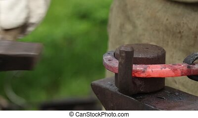 Smith makes a horseshoe on an anvil. Beats a hammer.