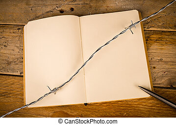 Censorship - Notebook and pen with barbed wire, a press...