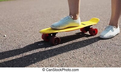 teenage girl right foot on short modern skateboard -...