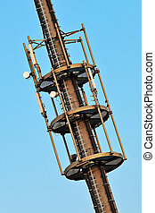 Telecommunication monopole tower section with antennas over blue sky.