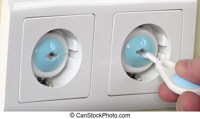 Hand remove safety plug from electricity socket and insert...