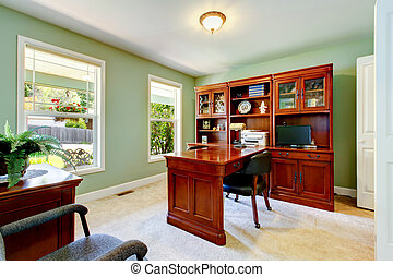 Interior of home office with ivory walls, desk and cabinet.