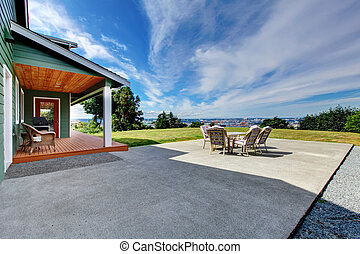 VIew of large concrete floor patio area with table set at backyard