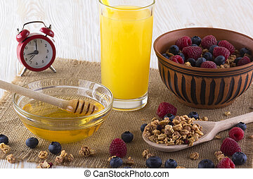 Muesli with fresh berries, orange juice, honey and alarm clock.