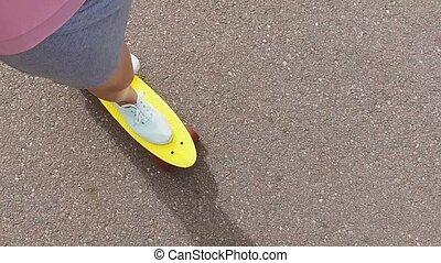 teenager girl riding short modern skateboard -...