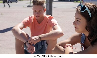 teenage couple with penny boards talking in city