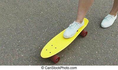 teenage girl toot putting short skateboard on end -...