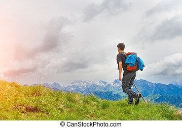 Boy walking in the mountains with his stick in the meadows...